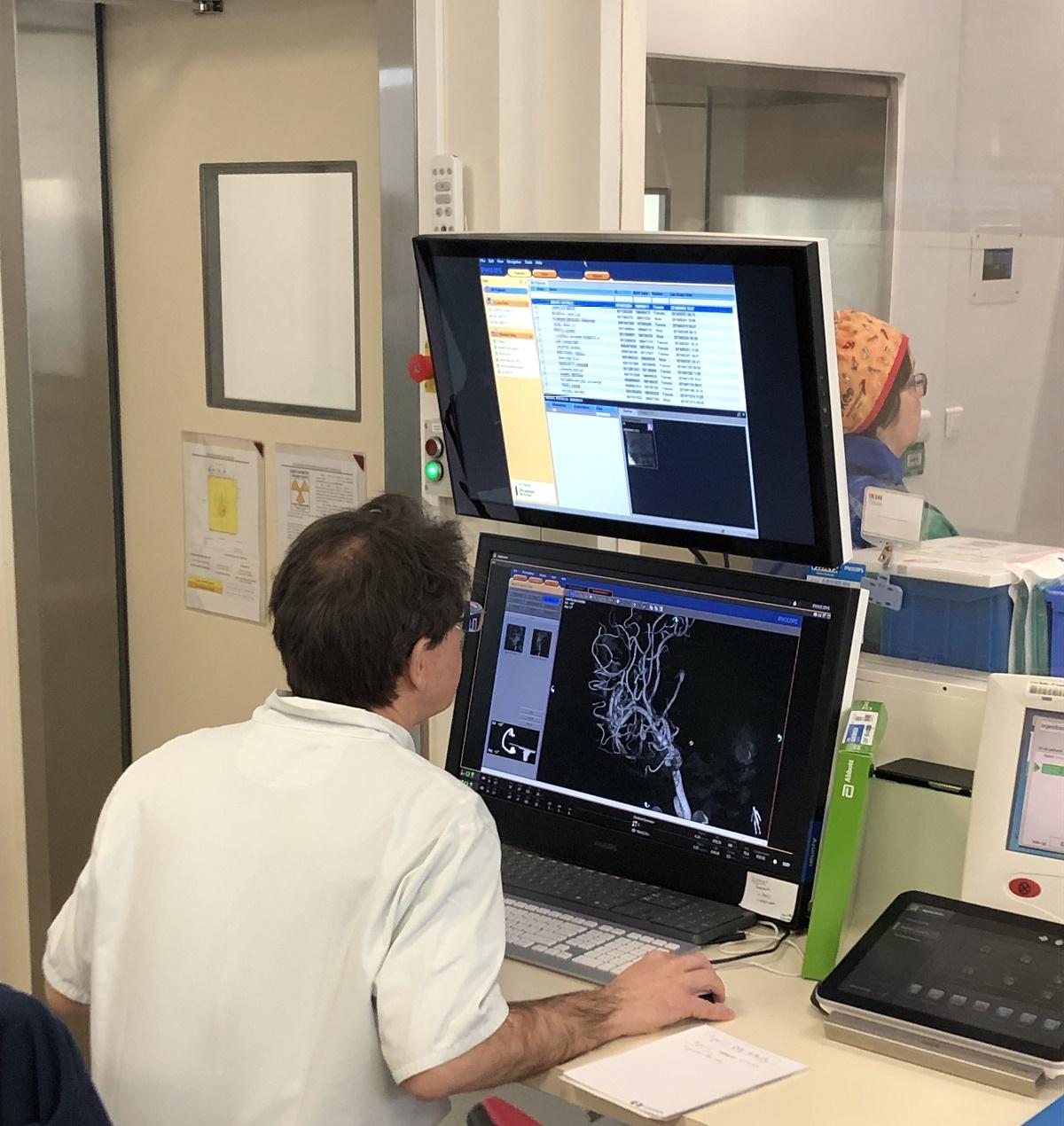 Le Pr Selle examine une imagerie 3D des vaisseaux cérébraux. Photo: Raphaël Moreaux/APMnews